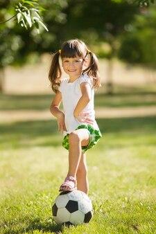 Bambina sveglia con una palla in un bellissimo parco