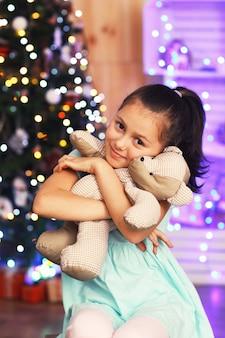 Bambina carina con orso vicino all'albero di natale