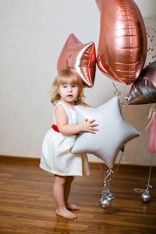 Bambina sveglia con decorazioni di compleanno
