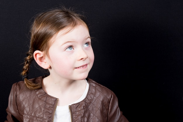 La bambina sveglia con capelli bobbed ha tagliato lo sguardo a partire dalla macchina fotografica