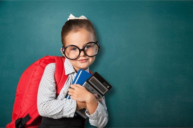 Bambina carina con libri sullo sfondo