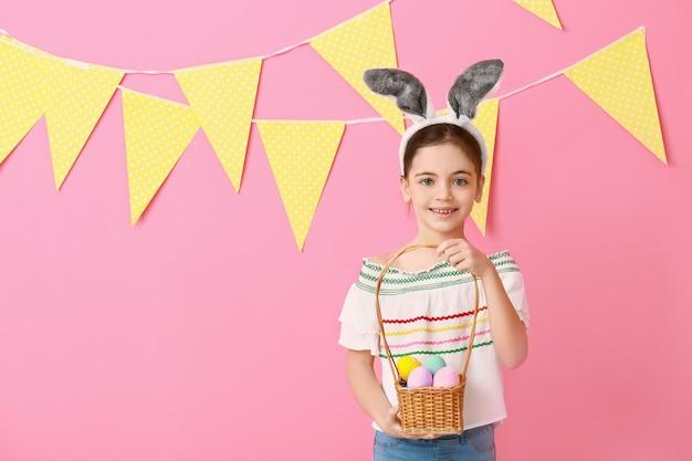 Bambina sveglia con orecchie da coniglio e uova di pasqua sulla superficie del colore