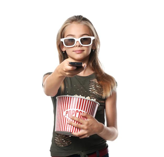 Bambina carina con una tazza di popcorn che cambia canale su superficie bianca white