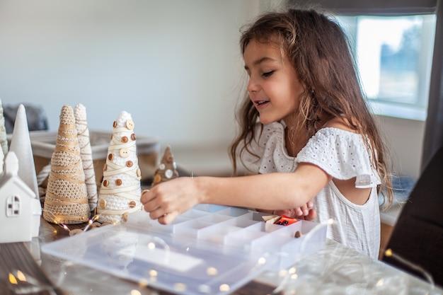 Bambina carina con i capelli ricci che fa mestieri e decora il cono dell'albero di natale con i bottoni