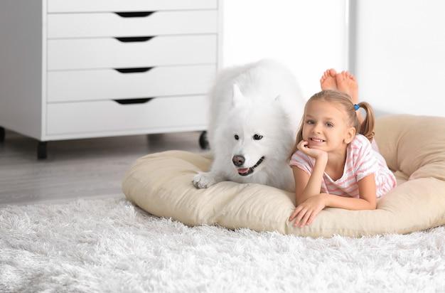 Bambina sveglia con il cane a casa