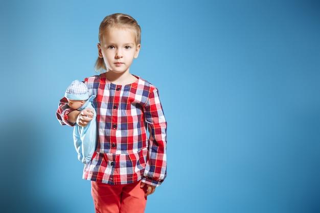 Bambina sveglia con la bambola sul blu