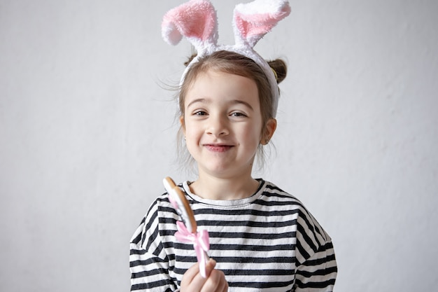 Bambina sveglia con pan di zenzero di pasqua su un bastone e orecchie da coniglio decorative sulla sua testa.