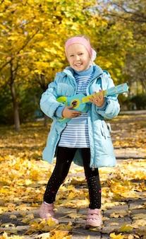 Bambina sveglia con un sorriso felice che sta all'aperto in un parco di autunno che gioca una chitarra del giocattolo