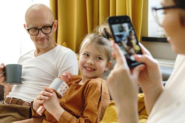 Bambina carina con un microfono da karaoke che canta per i suoi genitori a casa