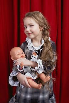 Bambina carina con lunghi capelli biondi con bambola audace tra le braccia negli stessi vestiti su