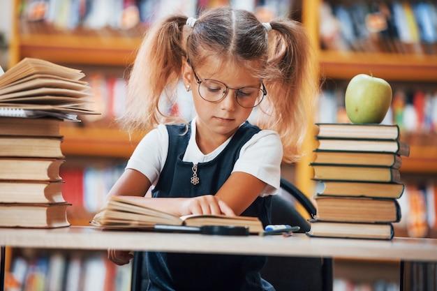 La bambina carina con le trecce è in biblioteca