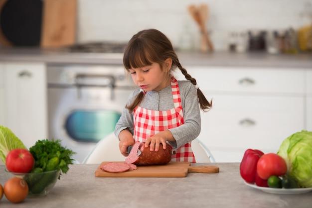 Una bambina carina con le trecce in un grembiule culinario scozzese taglia la salsiccia in panini in cucina al tavolo.