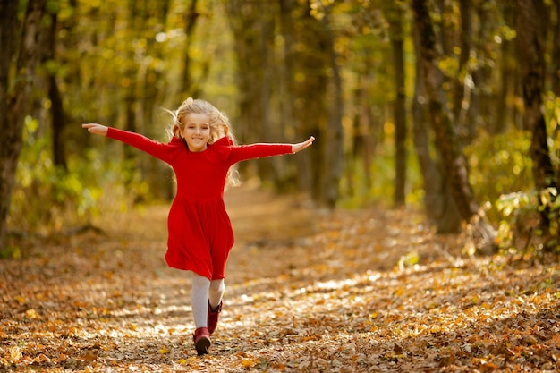Bambina sveglia con un vestito rosso nella foresta di autunno