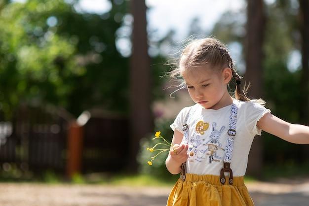 La bambina sveglia con un'emozione arrabbiata triste sul suo viso si trova da sola su una strada di campagna