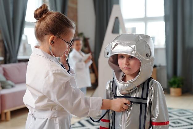 Bambina sveglia con lo stetoscopio che esamina l'astronauta in tuta spaziale