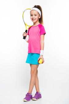 Bambina sveglia con la racchetta e la palla di tennis in sue mani su bianco