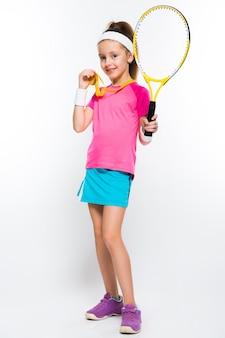Bambina sveglia con la racchetta e la medaglia di tennis in sue mani su fondo bianco