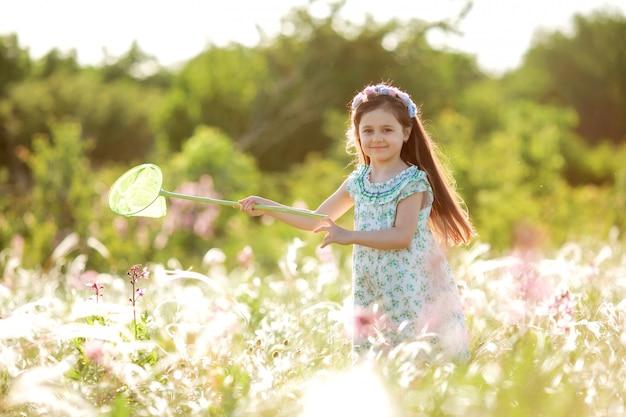 La bambina sveglia con una corona sulla sua testa cammina in un campo e prende la rete delle farfalle
