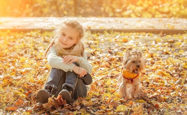 Bambina sveglia con yorkshire terrier nella sosta di autunno