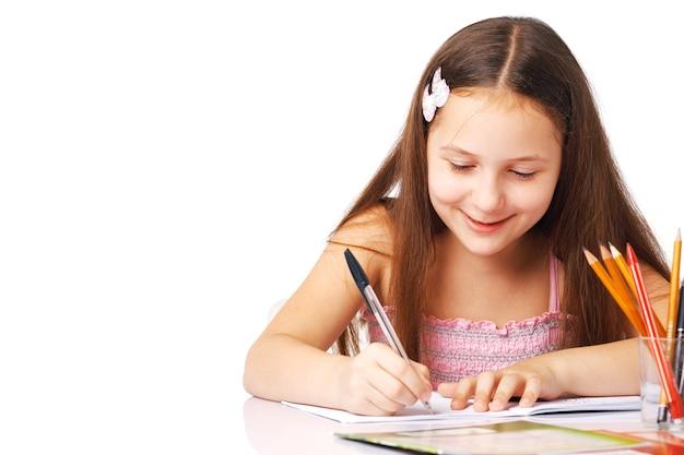 Bambina sveglia che scrive qualcosa nel quaderno e che sorride