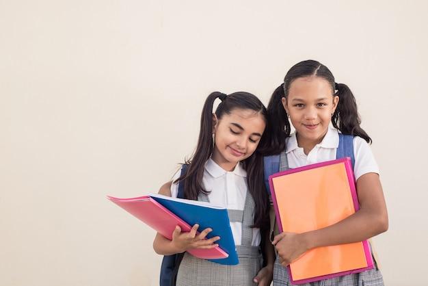 Bambine sveglie che indossano uniformi scolastiche