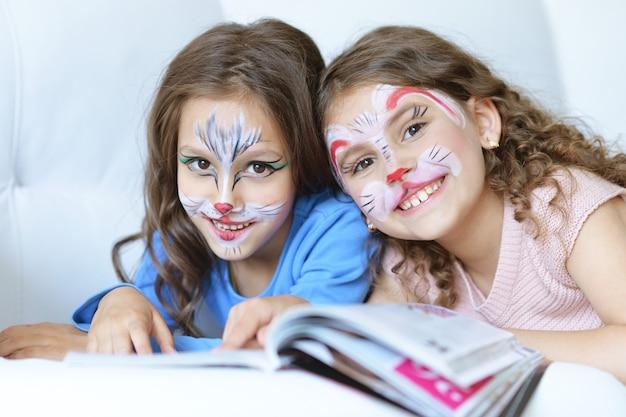 Bambine carine con il viso dipinto e rivista