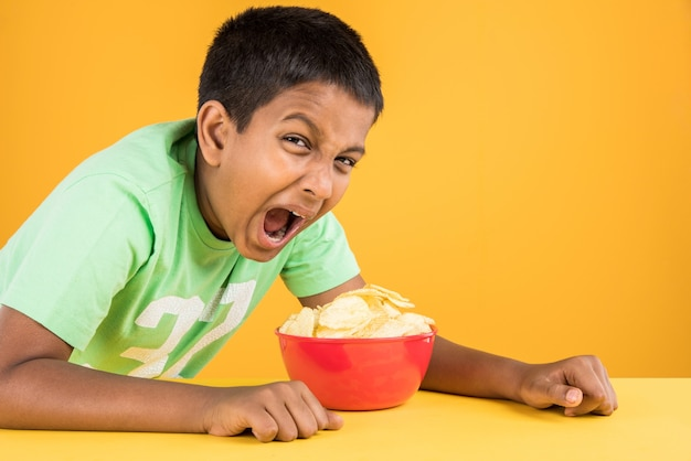 Carino piccolo ragazzo indiano o asiatico che mangia patatine o wafer di patate in una grande ciotola rossa, su sfondo giallo yellow