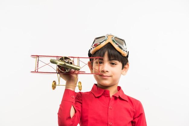 Simpatico ragazzino indiano o asiatico con aereo giocattolo su sfondo bianco