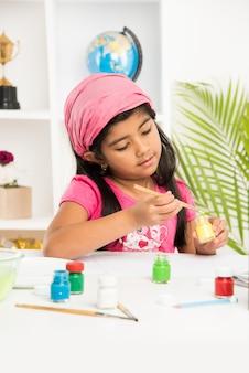 Carina bambina indiana o asiatica che si diverte a disegnare o dipingere con il pennello e dipingere su carta a casa