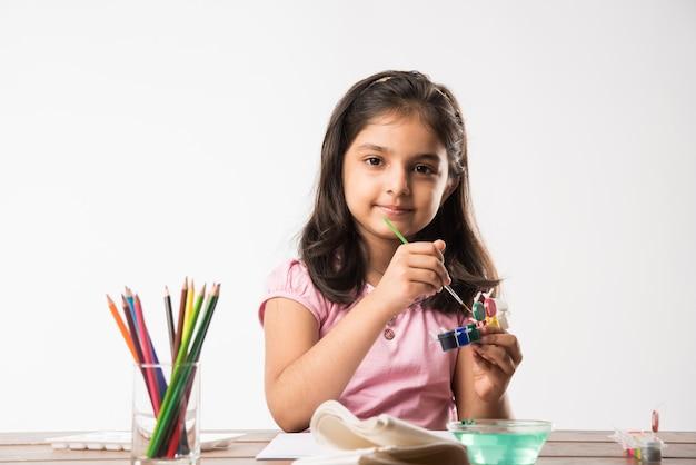 Simpatica bambina indiana o asiatica che colora, disegna o dipinge con colori, matite ecc