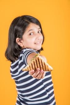 Carina bambina indiana o asiatica che mangia un gustoso hamburger, panino o pizza in un piatto o in una scatola. in piedi isolato su sfondo blu o giallo.