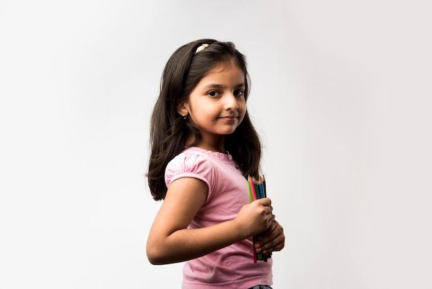 Carina bambina indiana o asiatica che tiene in mano matite colorate, in piedi isolata su sfondo bianco