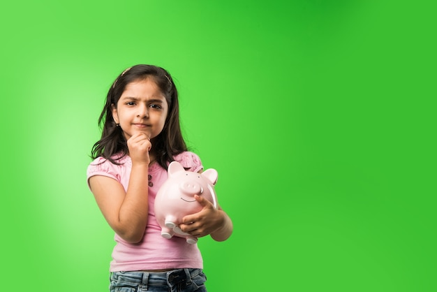 Carina bambina indiana o asiatica che tiene in mano un salvadanaio rosa e libri mentre si trova in piedi isolato su sfondo verde