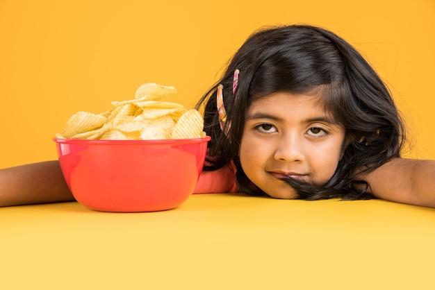 Carina bambina indiana o asiatica che mangia patatine o wafer di patate in una grande ciotola rossa, su sfondo giallo yellow Foto Premium