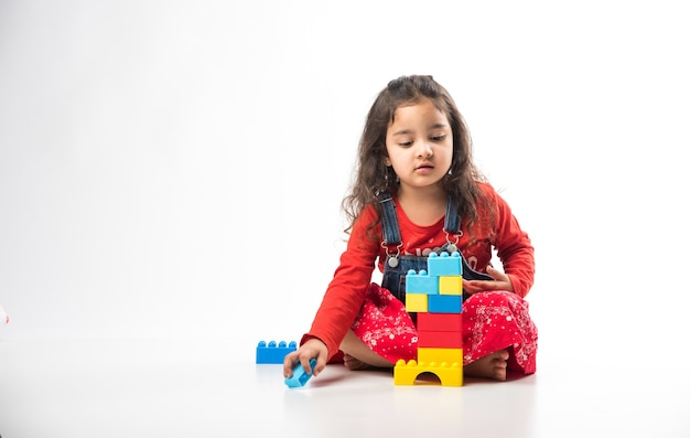 Carina piccola ragazza asiatica indiana che gioca con giocattoli a blocchi colorati su sfondo bianco