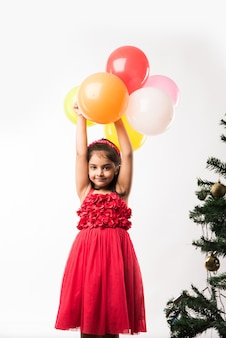 Carina bambina indiana o asiatica con palloncini colorati o gubbare in hindi, su sfondo bianco o rosso
