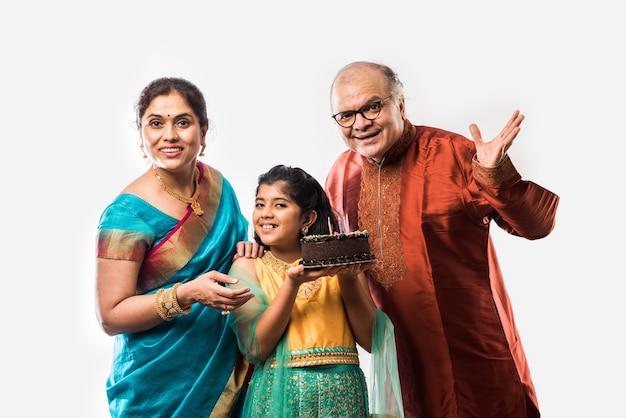 Piccola nipote o ragazza asiatica indiana carina che festeggia il compleanno con i nonni mentre indossa abiti etnici