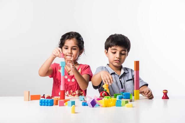 Simpatici bambini asiatici indiani che giocano con giocattoli o blocchi di plastica colorati mentre sono seduti a tavola o isolati su sfondo bianco