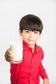 Simpatico ragazzo allegro indiano o asiatico che tiene o beve un bicchiere pieno di latte, isolato su sfondo bianco white