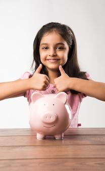 Carino piccolo indiano o asiatico con salvadanaio, mettendo monete, o pensando o mostrando i pollici in su. pianificazione per il futuro