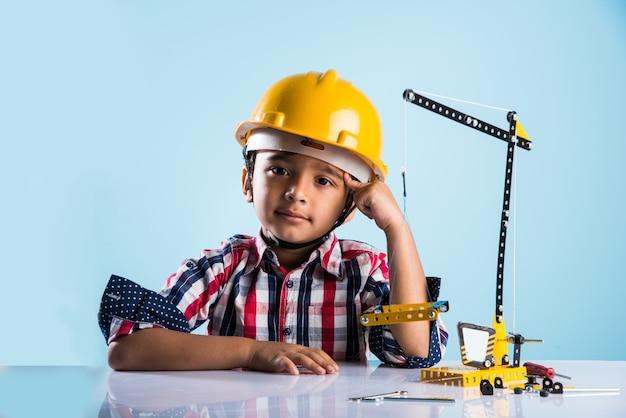 Simpatico ragazzino indiano che gioca con la gru giocattolo che indossa un cappello da costruzione giallo o un elmetto, concetto di infanzia e istruzione, isolato su lavagna verde
