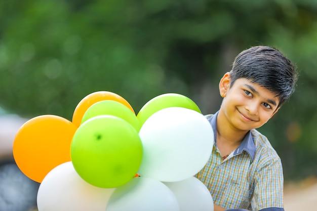 Ragazzino sveglio indiano con palloncini tricolore e celebra il giorno dell'indipendenza o della repubblica dell'india