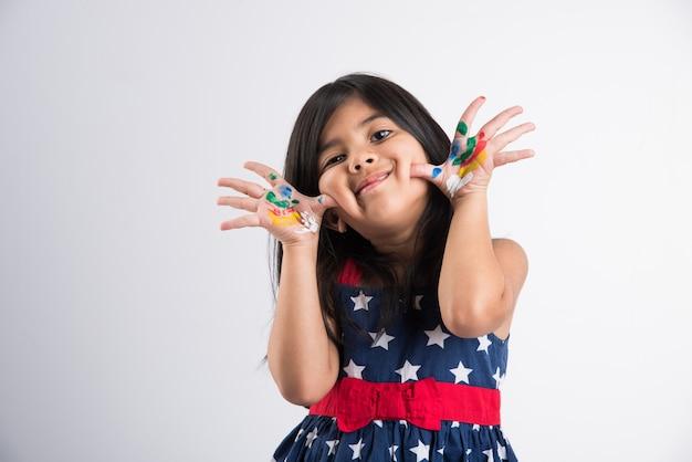 Carina bambina indiana che mostra le sue mani colorate o la stampa del palmo o la pittura o gioca al festival di holi con i colori, isolato su sfondo bianco