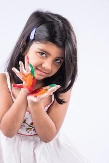 Carina bambina indiana che mostra le sue mani colorate o la stampa del palmo o gioca al festival di holi con i colori, isolato su sfondo bianco