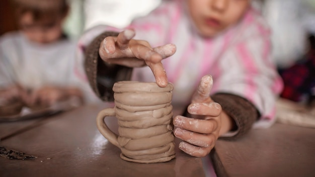 Simpatici bambini piccoli che giocano insieme con la modellazione di argilla nel laboratorio di ceramica, artigianato e arte dell'argilla