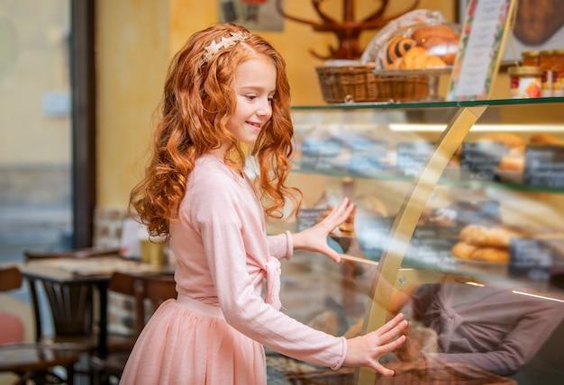 La piccola ragazza dai capelli rossi sveglia sceglie le torte alla finestra di vetro nella caffetteria