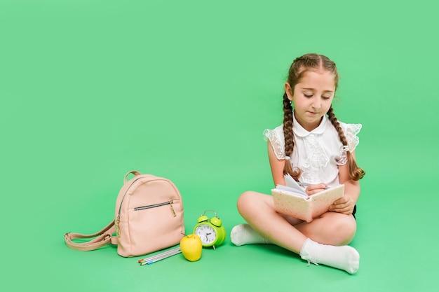 Carina scolaretta con borsa da scuola e accessori su sfondo verde