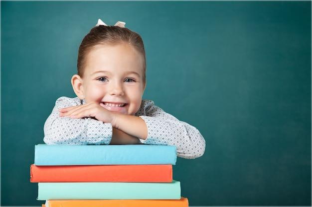 Piccola studentessa carina sullo sfondo della lavagna