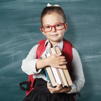 Piccola studentessa carina con gli occhiali sullo sfondo della lavagna