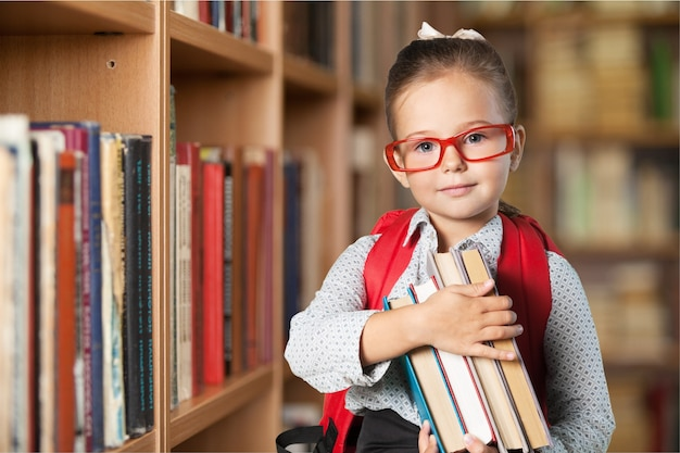 Piccola studentessa carina con gli occhiali sullo sfondo della biblioteca